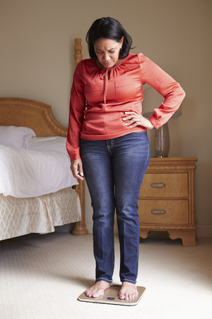 obeso: El sobrepeso mujer pesa en escalas en el dormitorio