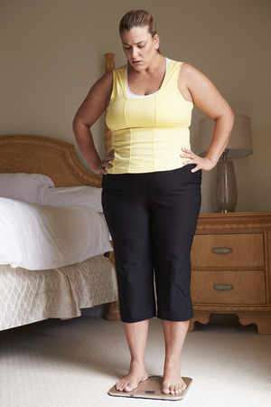 unhappy people: Overweight Woman Weighing Herself On Scales In Bedroom