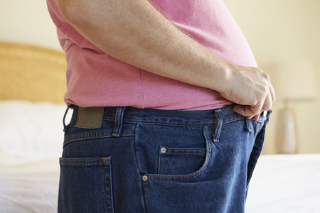 fasten: Close Up Of Overweight Man Trying To Fasten Trousers