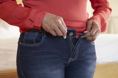 obeso: Cerca De Sobrepeso Mujer intenta sujetar los pantalones