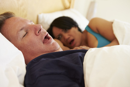 obeso: Pareja durmiendo en la cama con el hombre que ronca Foto de archivo