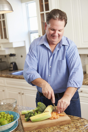 middle aged man: Overweight Man Preparing Vegetables in Kitchen