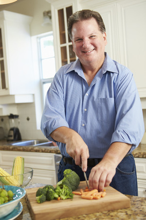middle age man: Overweight Man Preparing Vegetables in Kitchen