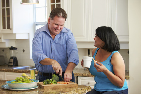 smiling man: Overweight Couple On Diet Preparing Vegetables In Kitchen