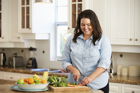 plus size woman: Overweight Woman Preparing Vegetables in Kitchen