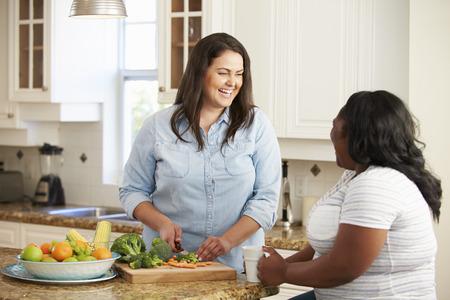 부엌에서 야채를 준비하는 다이어트에 두 중량이 초과 된 여성 스톡 콘텐츠