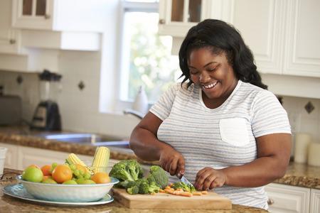太りすぎの女性が台所で野菜を準備