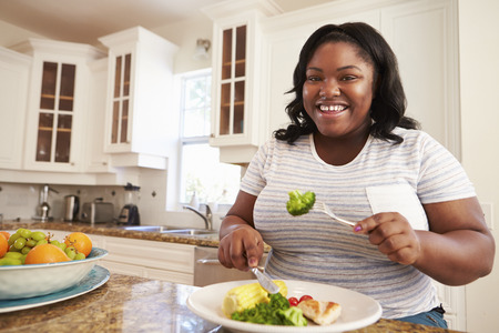 fat person: Overweight Woman Eating Healthy Meal in Kitchen