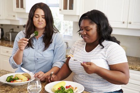 Two Overweight Women On Diet Eating Healthy Meal In Kitchen Stock Photo - 33519253