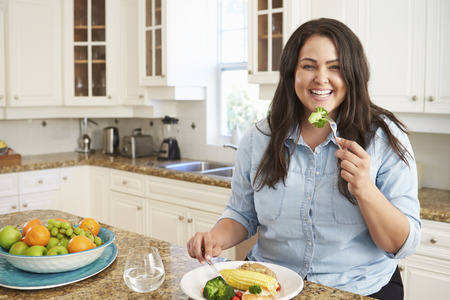Overweight Woman Eating Healthy Meal In Kitchen Stockfoto