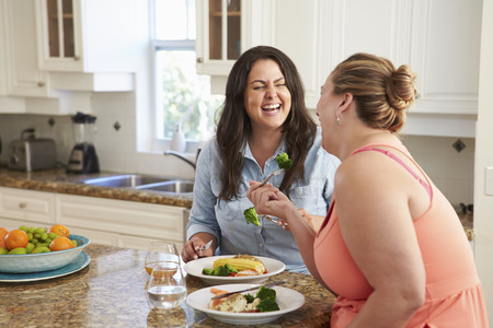 obeso: Dos mujeres con sobrepeso en dieta que come saludable comida en cocina