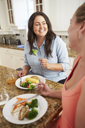fat: Two Overweight Women On Diet Eating Healthy Meal In Kitchen Stock Photo