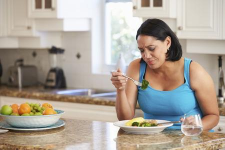 うんざりしてキッチンで健康的な食事を食べて太りすぎの女性