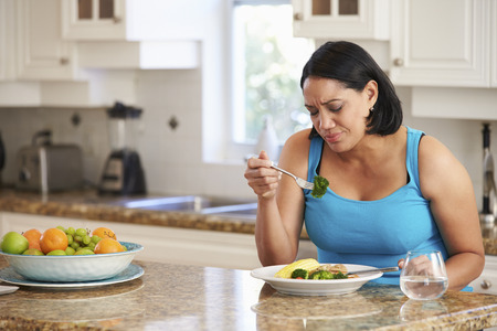 fat: Fed Up Overweight Woman Eating Healthy Meal in Kitchen Stock Photo