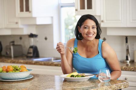 부엌에서 체중 여자 먹는 건강한 식사