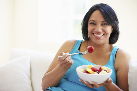 eating fruit: Overweight Woman Sitting On Sofa Eating Bowl Of Fresh Fruit Stock Photo