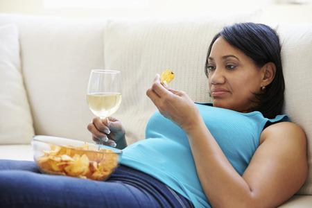 obeso: Mujer gorda en casa comiendo patatas fritas y beber vino