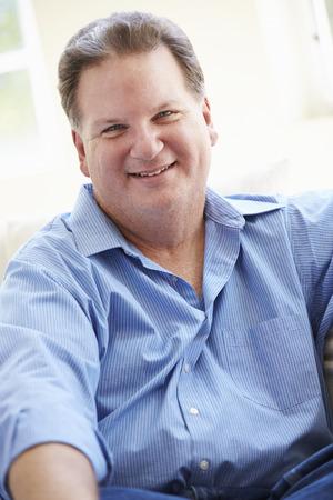 ソファの上に座って太り過ぎの男の肖像 写真素材