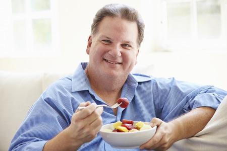 obesidad: Sobrepeso hombre sentado en el sof� comiendo plato de fruta fresca