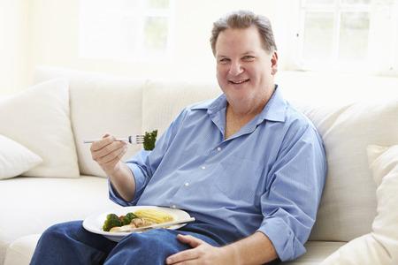 obeso: Hombre con sobrepeso comer comida saludable sentado en el sofá