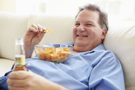 Overweight Man At Home Eating Chips And Drinking Beer Reklamní fotografie - 33519344
