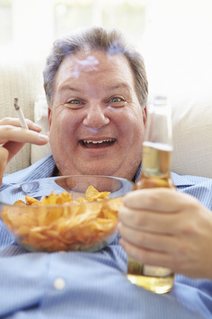 Overweight Man Eating Chips, Drinking Beer And Smoking Stock Photo