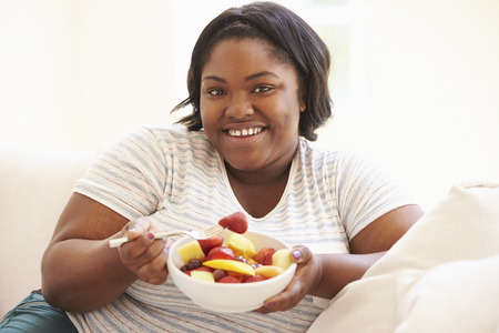 Overweight Woman Sitting On Sofa Eating Bowl Of Fresh Fruit Imagens