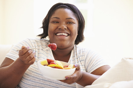 woman eating fruit: Overweight Woman Sitting On Sofa Eating Bowl Of Fresh Fruit Stock Photo