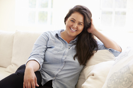 fat: Portrait Of Overweight Woman Sitting On Sofa Stock Photo