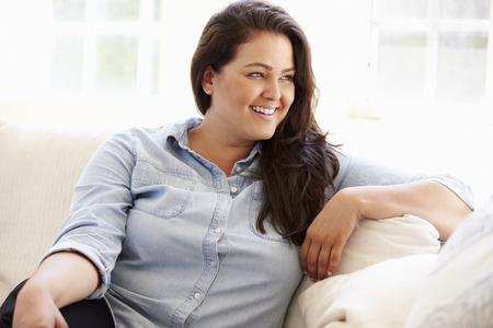 mujeres gordas: Retrato de mujer con sobrepeso sentado en el sofá