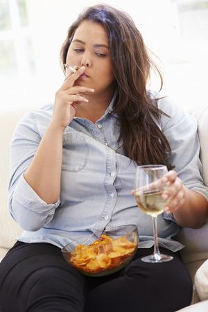 person sitting: El sobrepeso Mujer que come patatas fritas, beber vino y fumar Foto de archivo