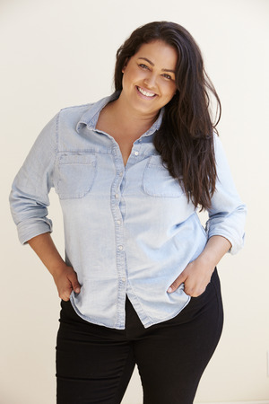 obese woman: Studio Portrait Of Smiling Overweight Woman Stock Photo