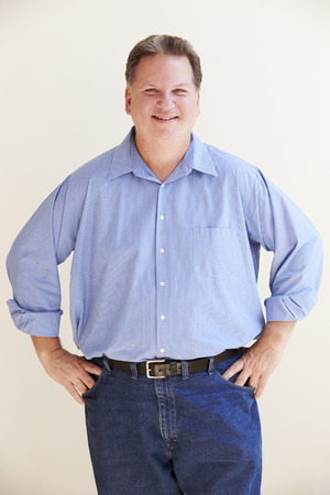 Studio Portrait Of Smiling Overweight Man
