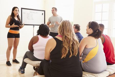alumnos en clase: Fitness Instructor Abordar las personas con sobrepeso En la dieta del Club Foto de archivo