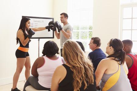 alumnos en clase: Instructor de acondicionamiento físico Abordar las personas con sobrepeso En Dieta Club de