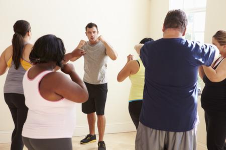 alumnos en clase: Instructor de acondicionamiento físico en la clase del ejercicio para personas con sobrepeso