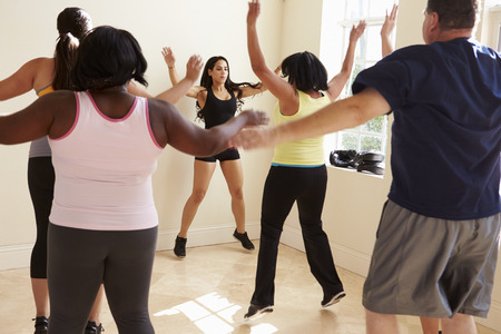 obesity: Fitness Instructor In Exercise Class For Overweight People