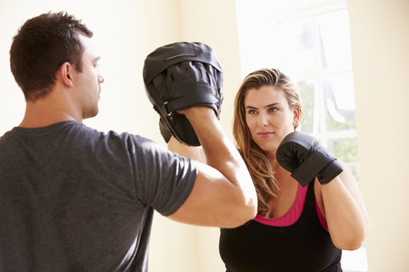 woman boxing gloves: Fitness Instructor Teaching Boxing In Exercise Class