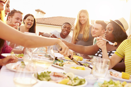 multi ethnic groups: Group Of Young People Enjoying Outdoor Summer Meal Stock Photo