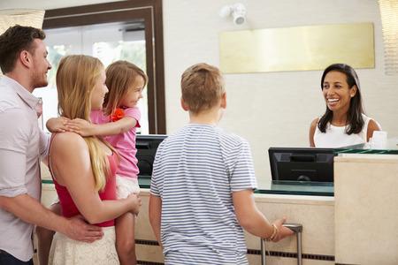 Familie Einchecken im Hotel Reception Standard-Bild