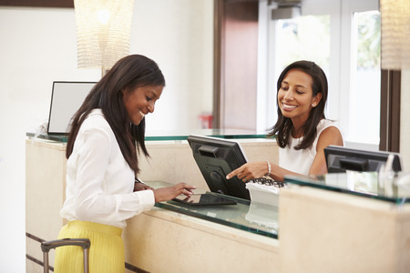front desk: Woman Checking In At Hotel Reception Using Digital Tablet Stock Photo