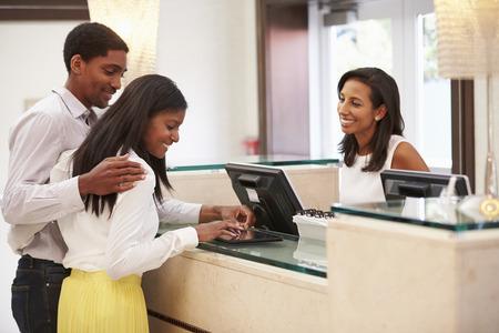 uomini di colore: Coppia check-in in Hotel Reception con tavoletta digitale Archivio Fotografico