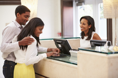 front desk: Couple Checking In At Hotel Reception Using Digital Tablet Stock Photo