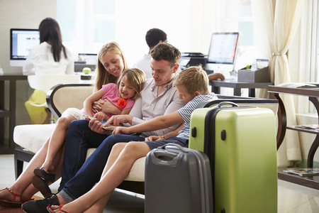 Family In Hotel Lobby Looking At Digital Tablet Stock Photo