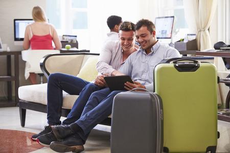 デジタル タブレットを見てのホテルのロビーに座っている男性のカップル