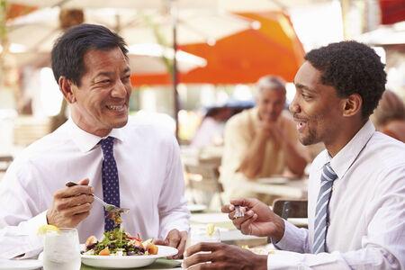 asian american: Two Businessmen Having Meeting In Outdoor Restaurant