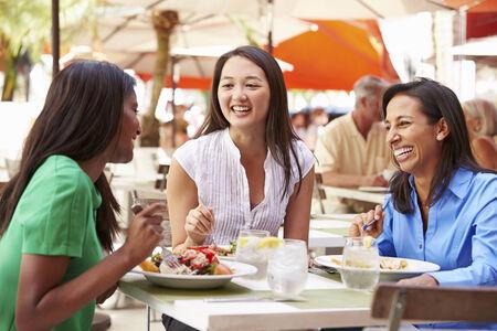 amigas conversando: Grupo de Amigos femeninos que disfrutan del almuerzo en restaurante al aire libre