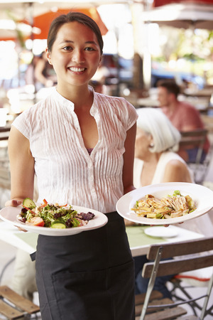 Waitress Serving Food At Outdoor Restaurant
