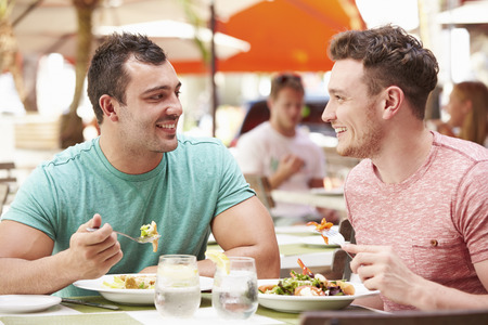 Male Couple Enjoying Lunch In Outdoor Restaurant Stock Photo