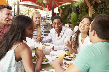 屋外レストランでランチを楽しんでいる友人のグループ